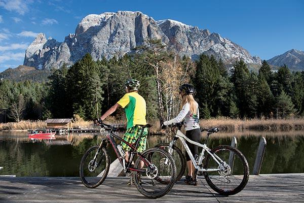 uomo e donna in bicicletta vicino a un torrente sotto lo sciliar