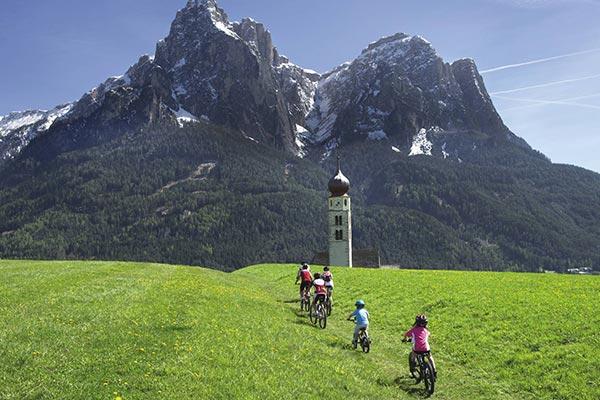 ciclisti sull'alpe di siusi di dirigono verso la montagna