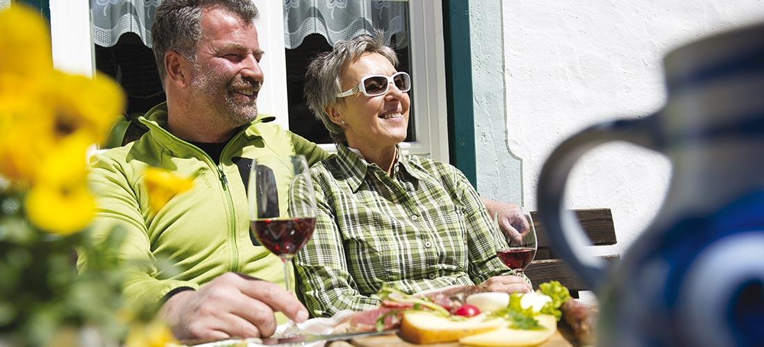 coppia sorseggia bicchiere si vino all'aperto in una giornata di sole
