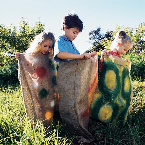 3 bambini fanno salto coi sacchi