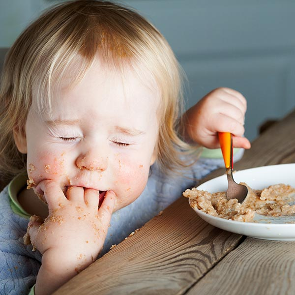 bambino piccolo che mangia con mano in bocca
