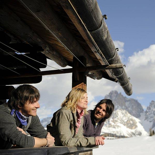 3 giovani si godono il panorama dello sciliar d'inverno