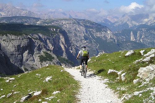 Ciclista in mountain bike su un sentiero sterrato delle Dolomiti in Trentino Alto Adige
