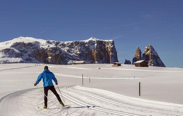 Un uomo pratica lo sci da fondo all'Alpe di Siusi, sullo sfondo si vede il massiccio dello Sciliar