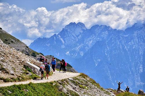 Gruppo di persone cammina su un sentiero in Trentino, sullo sfondo si vedono le Dolomiti