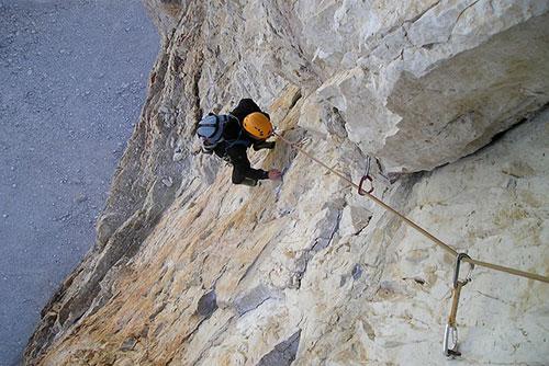 Un uomo si arrampica con una corda di sicurezza su una parete rocciosa del percorso delle tre cime sulle Dolomiti