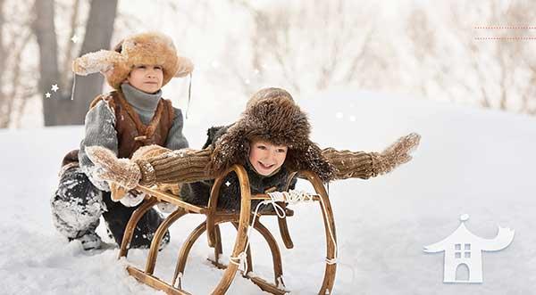 2 bambini giocano su una slitta sulla neve