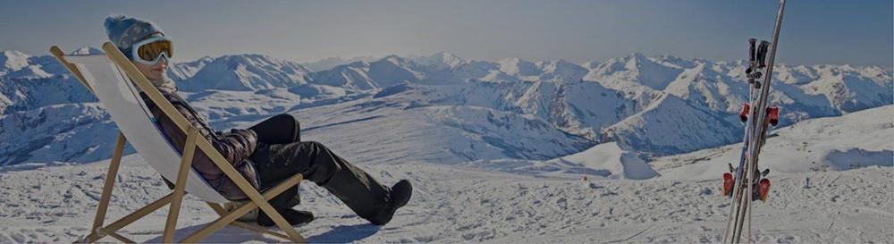 Sciatore seduto su una sedia a sdraio ammira paesaggio delle Dolomiti all'Alpe di Siusi